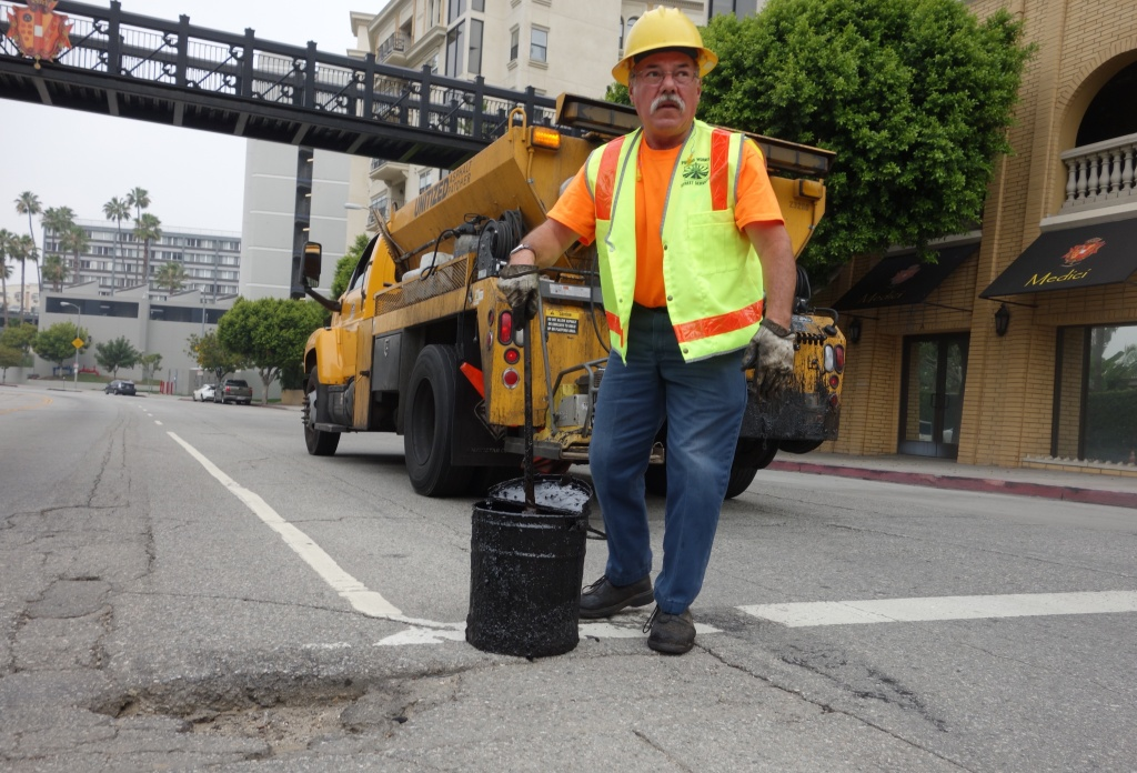Los Angeles city worker Hugo Vasquez reviews a pothole that needs filling at 8th Street and Bixel Ave. downtown.