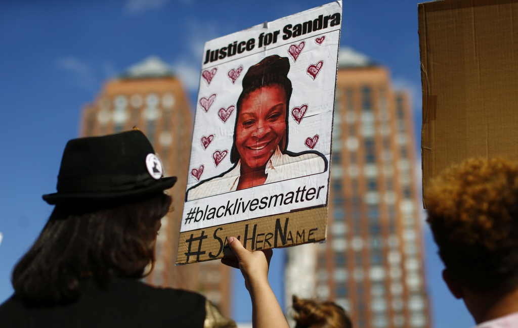 A woman holds a poster bearing the portrait of  Sandra Bland, a 28-year-old black woman who killed herself in a Texas jail cell on July 13th, during a Michael Brown memorial rally on Union Square August 9, 2015 in New York.