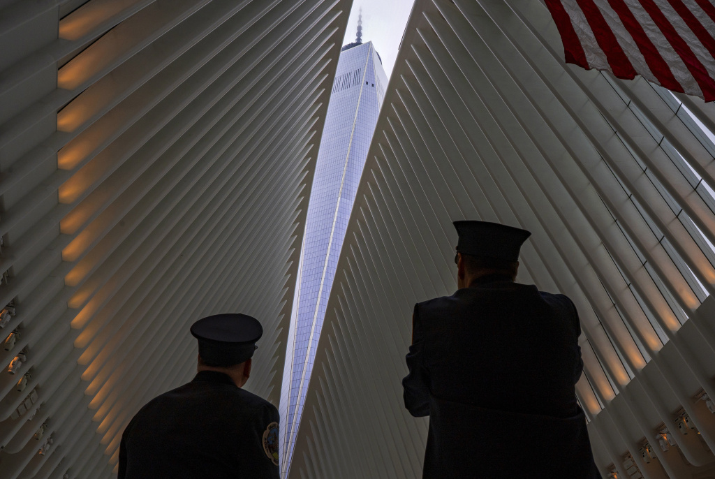 Two members of the New York City Fire Department look through the open ceiling of the Oculus, part of the World Trade Center transportation hub in New York on Tuesday. The transit hall ceiling window was opened just before 10:28 a.m., marking the moment that the North Tower of the World Trade Center collapsed on Sept. 11, 2001.