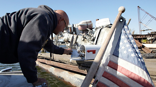 Rick Stelzreide leans over the side of his boat to deliver a Delta resident's mail.