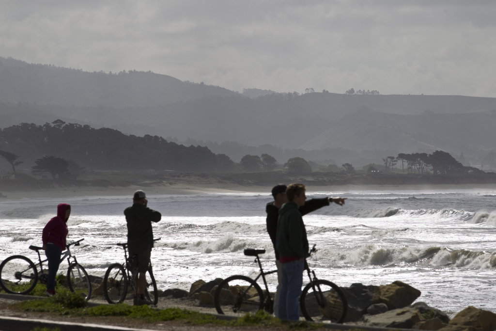 People watch from a road above a beach as tsunami surges hit on March 11, 2011 in Half Moon Bay, California. A tsunami warning for Northern California has been issued and a voluntary evacuation is in effect in Half Moon Bay.