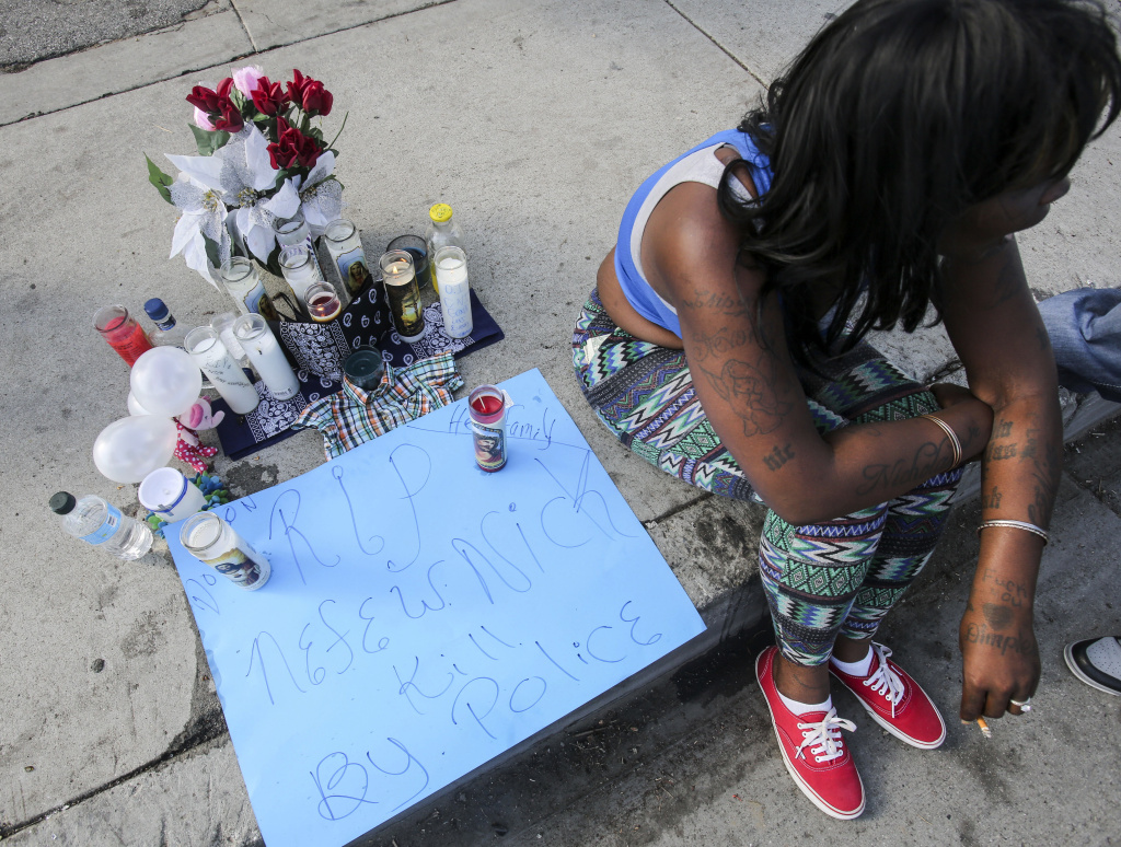 A woman sits next to a makeshift memorial set up Sunday, Dec. 13, 2015, for a man who was shot and killed by Los Angeles County Sheriff's deputies Saturday near a gas station, in Lynwood, Calif. A black man who was fatally shot by Los Angeles deputies kept holding a gun as he lay dying on the ground, authorities said Sunday in response to questions about why they continued to fire on the man after he fell to the pavement.
