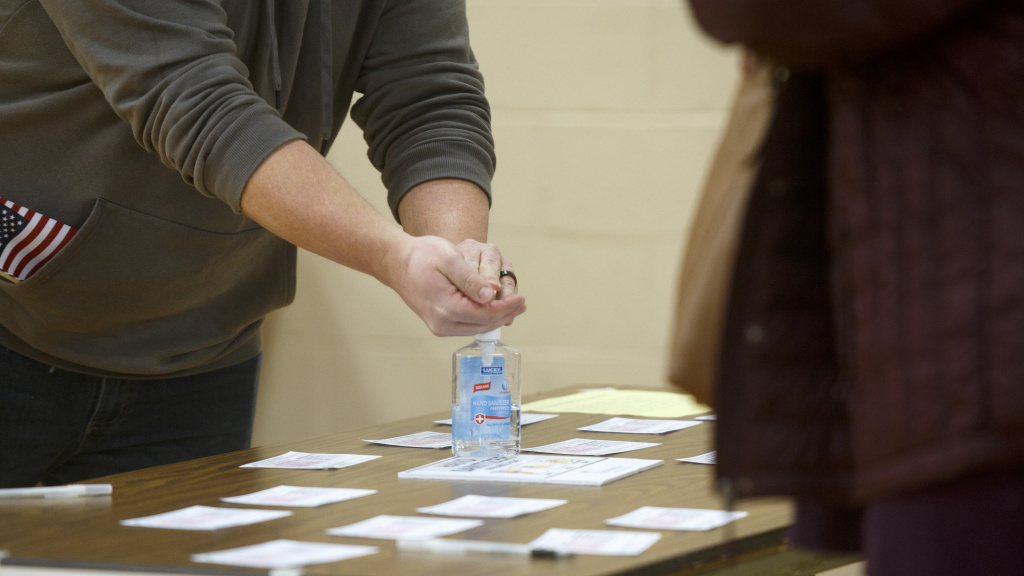 A Michigan voter uses hand sanitizer that the polling place provided after casting his ballot at Warren Woods Baptist Church in Warren, Mich., last week.