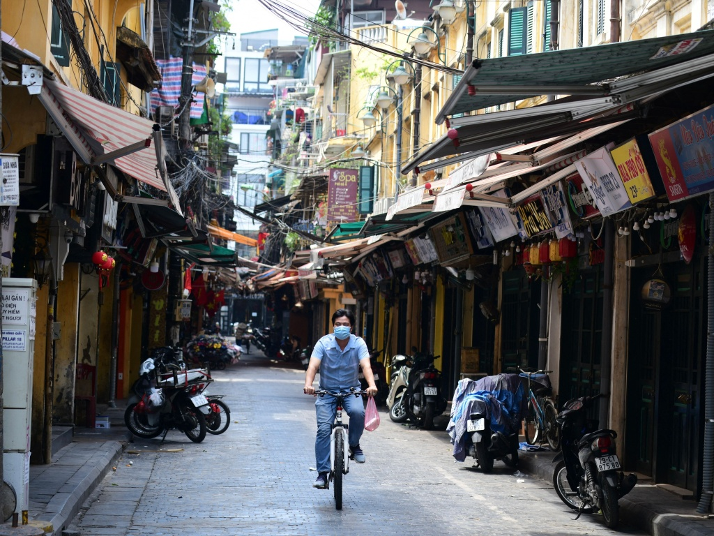 A man rides a bicycle on an empty street amid lockdown restrictions due to a surge in COVID-19 cases in Hanoi on May 10. On Saturday, Vietnam's health ministry announced the discovery of a new coronavirus variant in the country.