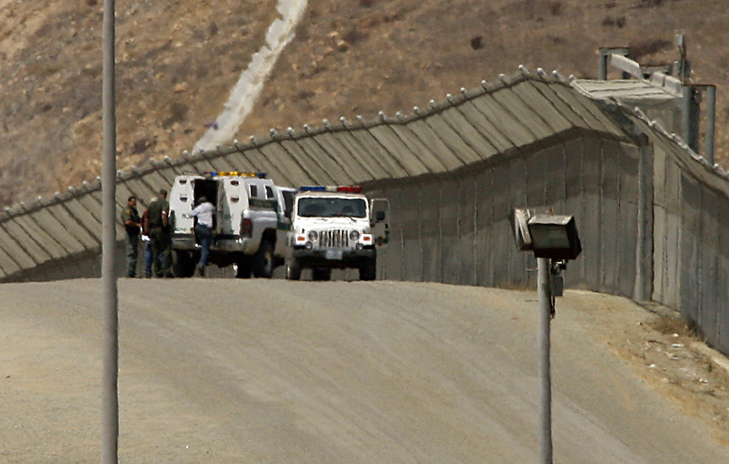 U.S. Border Patrol agents arrests a migrant attempting cross illegally along the border fence in San Ysidro, Cailf. A comprehensive immigration reform bill approved last week by the Senate calls for costly border security enhancements, which federal contractors would provide much of.