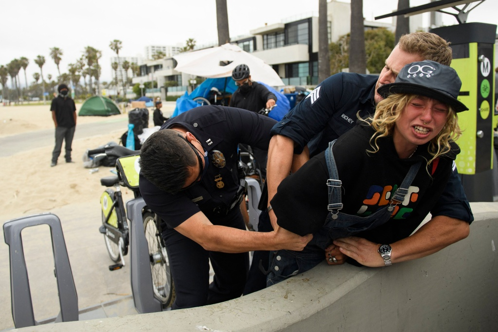 Los Angeles Police Department officers wrestle a knife away from a person experiencing homelessness during an event with Los Angeles City Council Member and mayoral candidate Joe Buscaino at Venice Beach on June 7, 2021 in Los Angeles, California.