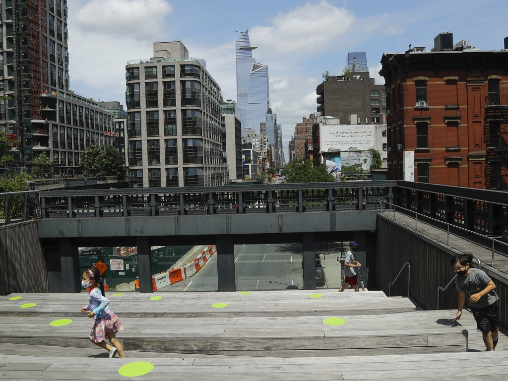 New York City Mayor Bill de Blasio announced the city will offer free child care to 100,000 students when schools re-open for part-time in-person instruction in September. Here, children play at Manhattan's High Line park on Thursday.