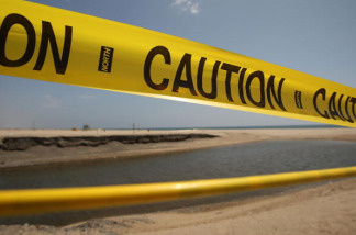 A barrier of caution tape warns beach-goers to stay out of the water, which is polluted by run-off from a nearby storm drain and creek, at Will Rogers State Beach on May 22, 2009 in Pacific Palisades, California.