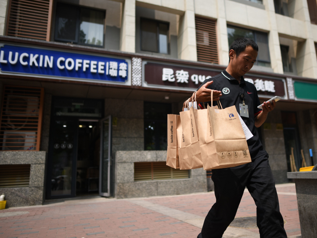 Luckin Coffee customers use an app and can pick up their coffee in 3 minutes or have it delivered. Above, a deliveryman in Beijing.