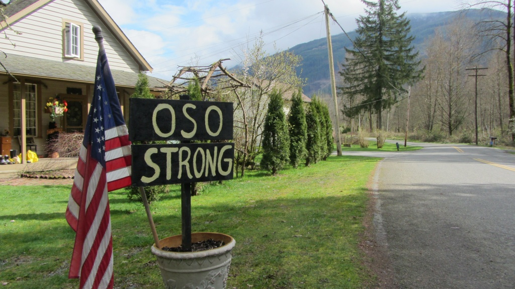 A sign and the American flag are seen in Oso, Washington on March 31, 2014. 'We're still in shock, really,' says Ben Sullivan. As the likely death toll from the monster landslide in the picture postcard valley town of Oso climbs into the dozens, that's a common feeling round here, more than a week after the catastrophe.