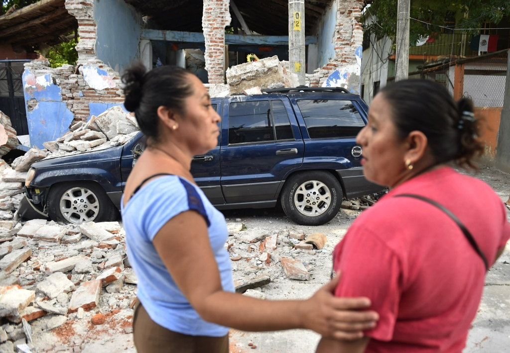 Two women stand in front of a damaged building after an 8.1 magnitude earthquake that hit Mexico's Pacific coast on September 7, 2017 in Juchitan de Zaragoza, Oaxaca.