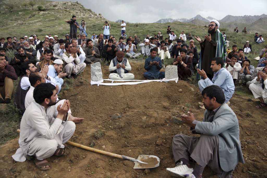 Relatives, colleagues and friends pray next to the grave of AFP chief photographer, Shah Marai, who was killed in today's second suicide attack, in Guldara, a district of Kabul province, Afghanistan, Monday, April 30, 2018. A coordinated double suicide bombing by the Islamic State group in central Kabul has killed at least 25 people, including several Afghan journalists.