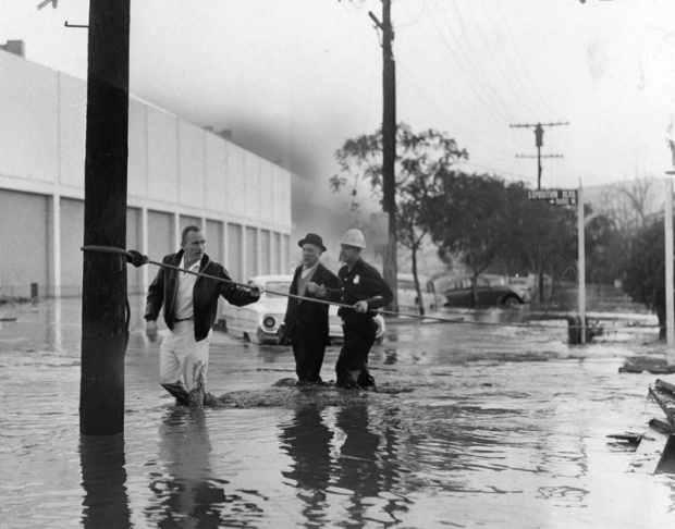 Firemen escort flood victims in Baldwin Hills in the aftermath of the Baldwin Hills Dam disaster. They wade through the street using a safety rope.