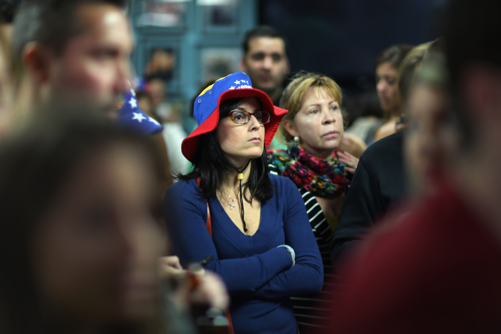 A crowd watches televised reports on the death of Venezuelan president Hugo Chavez at El Arepazo 2, a restaurant in Doral, Florida, a neighborhood with the largest concentration of Venezuelan immigrants in the U.S. March 5, 2013.