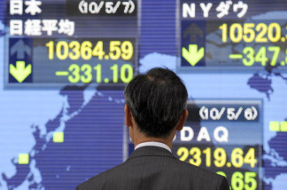 A pedestrian checks the share prices on the indicator at the window of a securities company in Tokyo, on May 7, 2010. The headline Nikkei index of the Tokyo Stock Exchange closed 331.10 points lower at 10,364.59, a two-month closing low, the second consecutive day of sharp declines after Wall Street saw a record drop due to the Greek debt crisis.