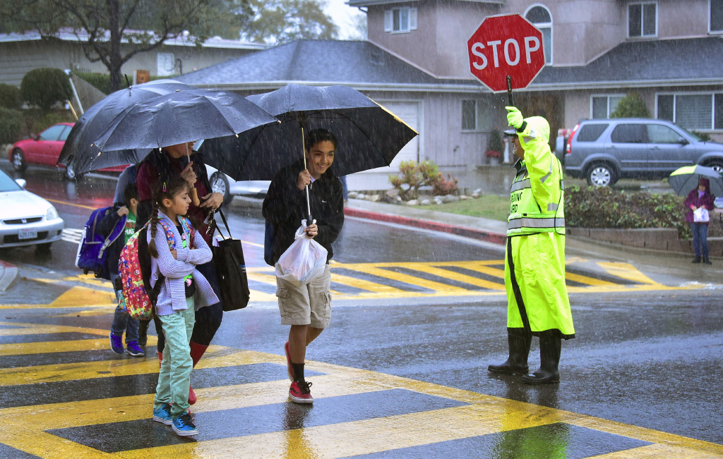 A school crossing guard holds up a sign to stop traffic as students and parents walk in the rain on Dec. 16, 2016 in Monterey Park as the biggest rain storm of the season hits Southern California.