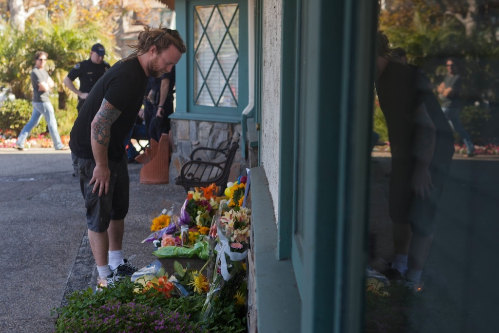 A mourner places flowers at the site of a mass killing in Seal Beach that took place the day before on October 12, 2011. A stream of people stopped by throughout the day to grieve.