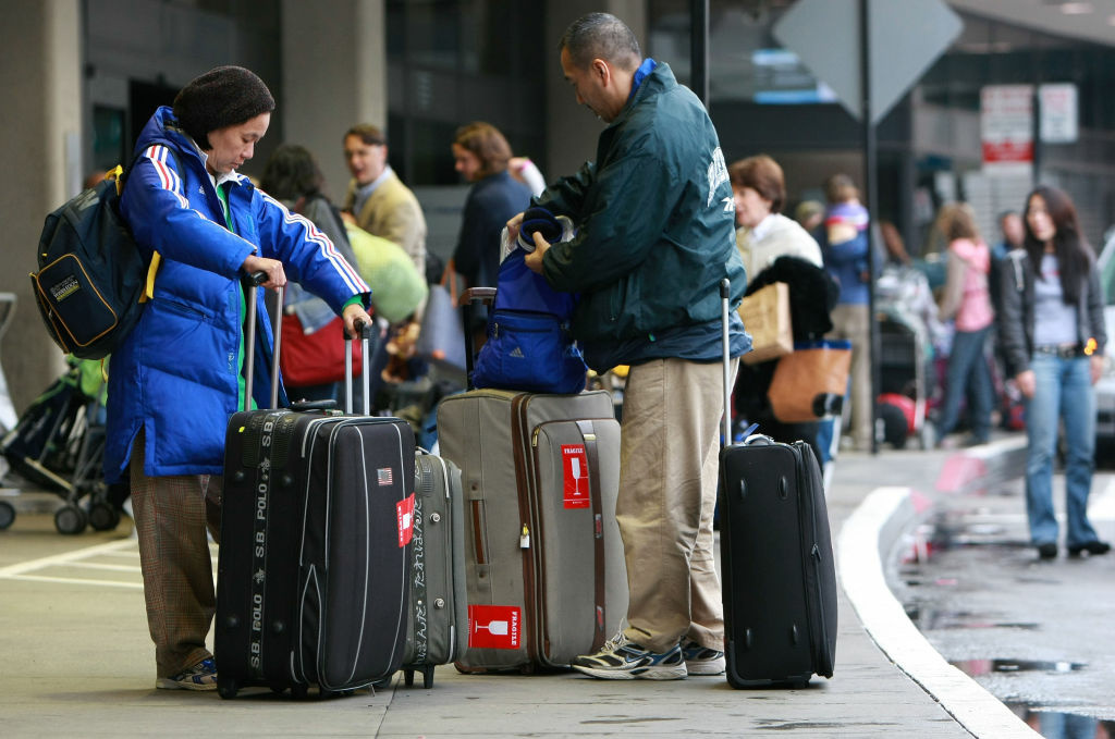 Travelers gather their luggage before checking in for a flight at San Francisco International Airport in San Francisco, California.