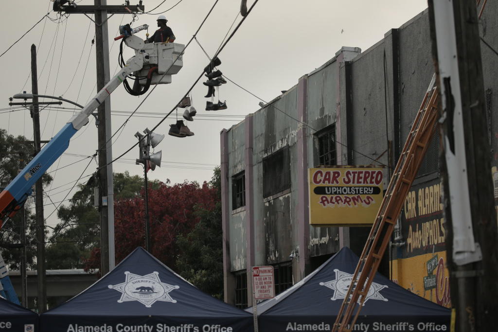 A man works with a power pole in front of a warehouse where a fire claimed the lives of at least thirty-six people on December 5, 2016 in Oakland, California.