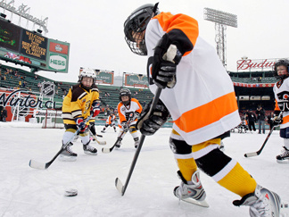 Youth teams play on an auxiliary outdoor rink before the 2010 New Year's Day Winter Classic NHL hockey game. New research shows that young players in leagues that allow checking are much more likely to suffer concussions and serious injuries than kids who play in leagues that ban it.