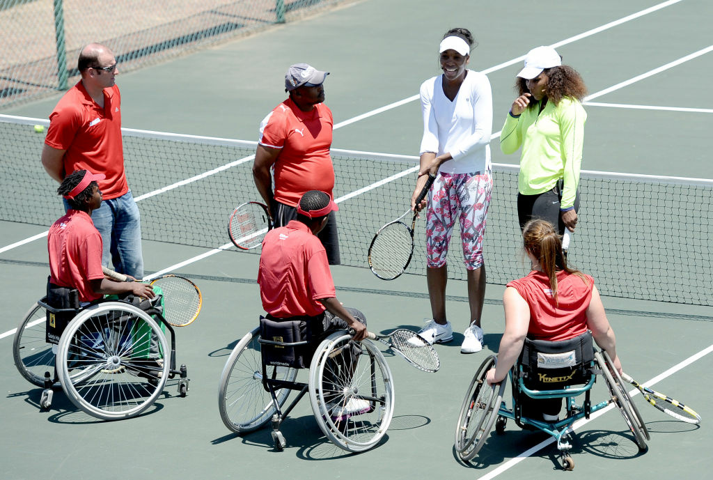 US tennis star Venus Williams (1stR) and her sister Serena Williams (2ndR) participate on November 3, 2012 in a two-hour tennis clinic with disabled children in wheelchairs at the Arthur Ashe Academy in Soweto.