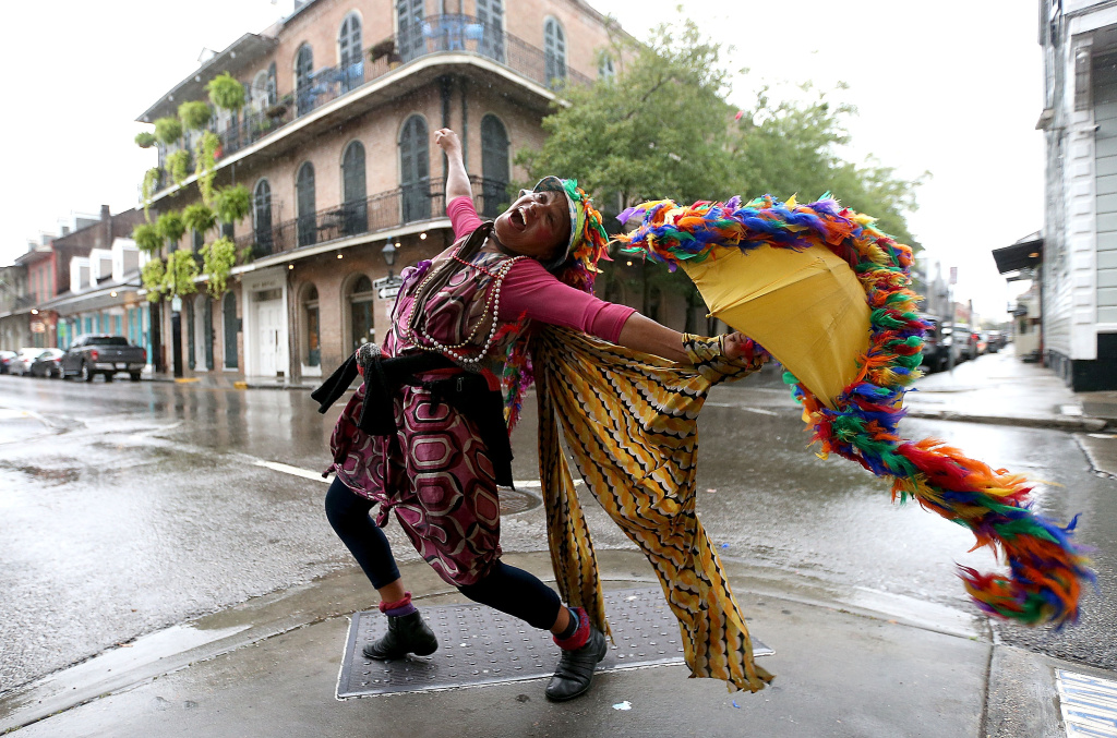 A woman dances in the street in New Orleans's French Quarter as heavy rain from Hurricane Nate begin comes down on Saturday, October 7, 2017.