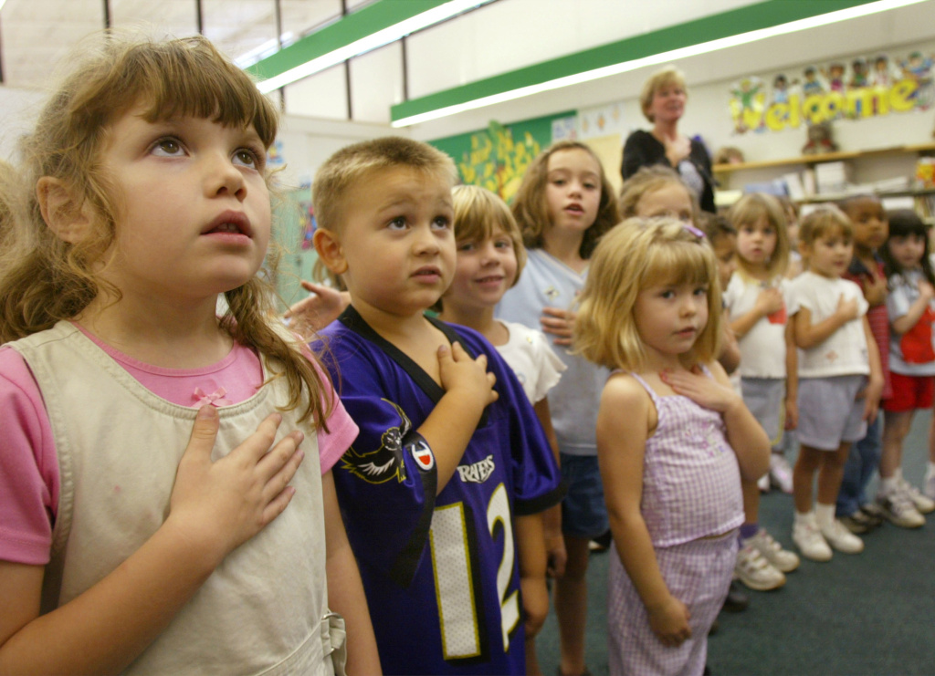 Sarah Henderson (L) and children from Mrs. Morrow's kindergarten class at Sunderland Elementary school recite the Pledge of Allegiance September 17, 2002 in Sunderland, Maryland. At the 2014 National Governors Association meetings, Maryland was held up as an example of a state where early education is working well, preparing children for the rigors of kindergarten.