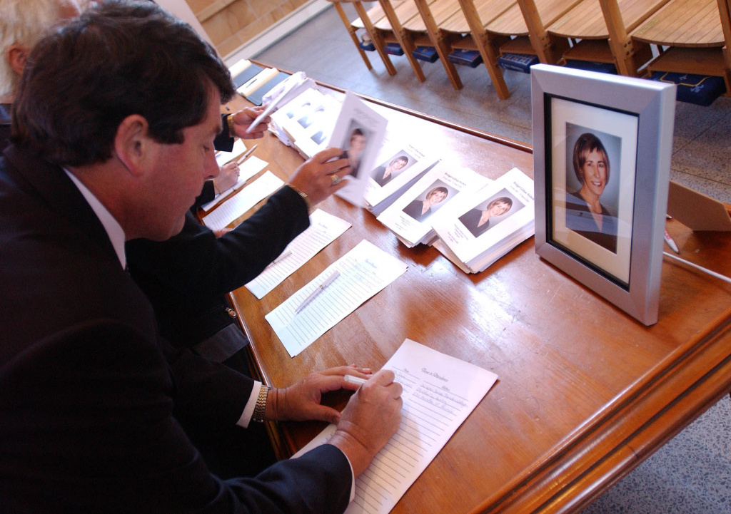 A congregation signs the attendance register at a funeral in Wellington Cathedral in Wellington, New Zealand on March 26, 2002.