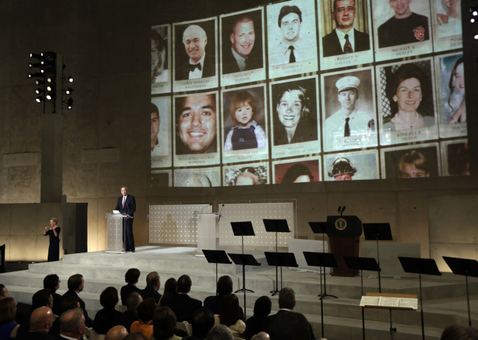 Former New York Gov. George Pataki speaks as photos of 9/11 victims are projected during the dedication ceremony in Foundation Hall at the National September 11 Memorial Museum at ground zero May 15, 2014 in New York City.
