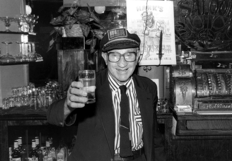 The late proprietor toasts photographer Gary Leonard at Hank's Bar in downtown Los Angeles.