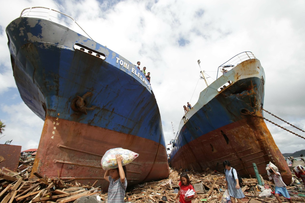 In this file photo, survivors pass by two large boats after they were washed ashore by strong waves caused by Typhoon Haiyan in Tacloban city, Leyte province central Philippines on Sunday, Nov. 10, 2013. Typhoon Haiyan, one of the strongest storms on record, slammed into six central Philippine islands on Friday leaving a wide swath of destruction and hundreds of people dead. A rise in sea levels is leading to increasing damage from storm surges and coastal flooding, as demonstrated by Typhoon Haiyan, the head of the U.N. weather service said Monday.