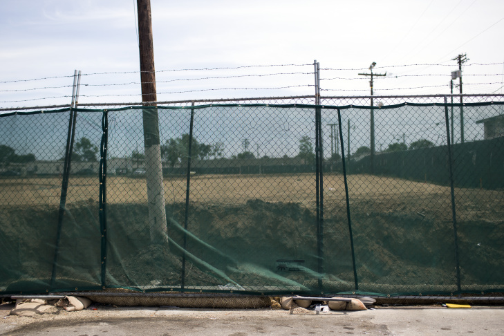 The chain link fence, covered with green mesh to contain dirt, separates Jordan Downs from the site of the old steel mill.