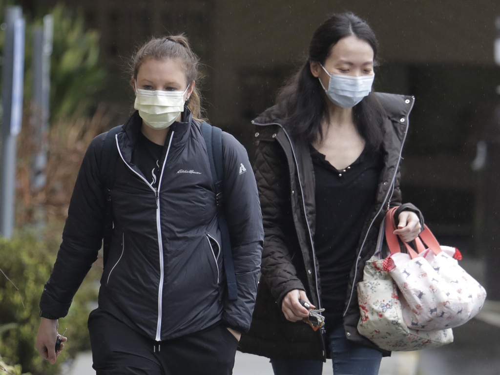 Two women wearing masks walk away from the Life Care Center in Kirkland, Wash., near Seattle, where health officials are monitoring patients. An outbreak of the coronavirus is cited as the cause for two  deaths of patients who received care at the center.