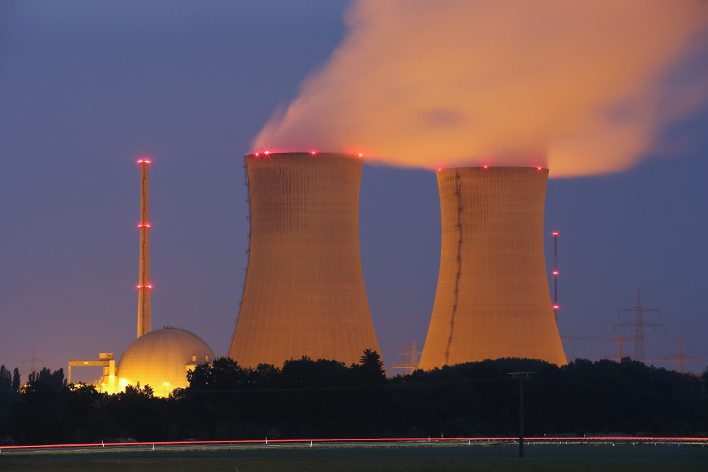 Passing cars leave a streak of light as steam rises from the cooling towers of the Grafenrheinfeld nuclear power plant at night on June 11, 2015 near Grafenrheinfeld, Germany.