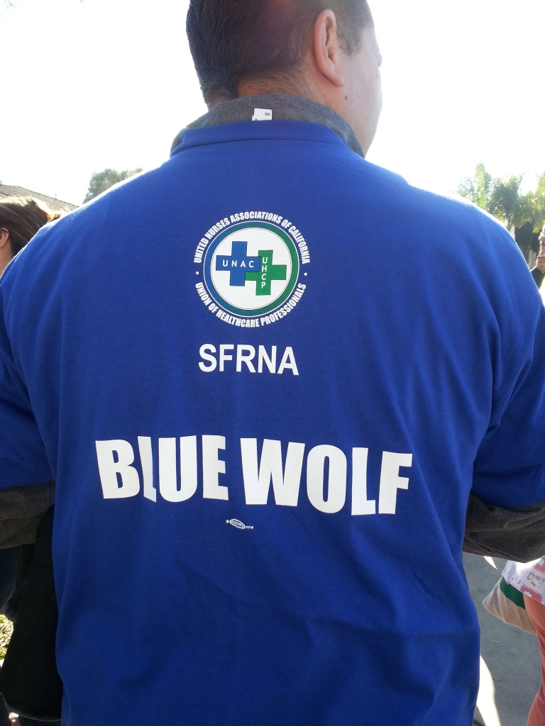 A member of a healthcare workers union wears a t-shirt in favor of Blue Wolf Capital during a January protest of the sale of Daughters of Charity hospitals to Prime Healthcare. In March Prime backed out of the deal and Blue Wolf expressed interest in the chain.