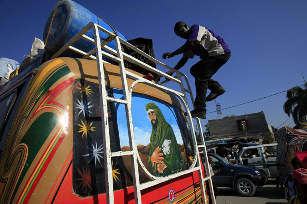 A man walks down a bus that has a painting on its back of Israel's King David in Port-au-Prince, Tuesday, March 30, 2010. The Haitian government will be seeking about $3.8 billion at a United Nations donors conference Wednesday to help the country recover from its Jan. 12 earthquake.