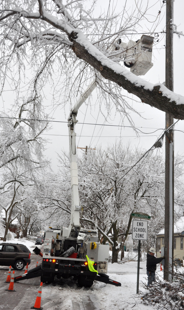 An Xcel Energy crew works to restore a storm-damaged power line on Friday in Sioux Falls, S.D. More than 18,000 homes in the region were without power after a major spring storm brought freezing rain and heavy snow that downed trees and power lines.