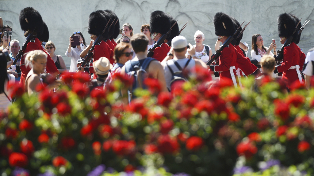 Spectators gather daily to watch the Changing the Guard at Buckingham Palace in London. On Friday, a military band paid tribute to Aretha Franklin at the ceremony.