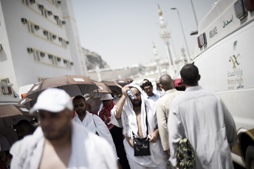 Muslim pilgrims walk past Saudi ambulances carrying injured pilgrims at an emergency hospital in Mina, near the holy city of Mecca.