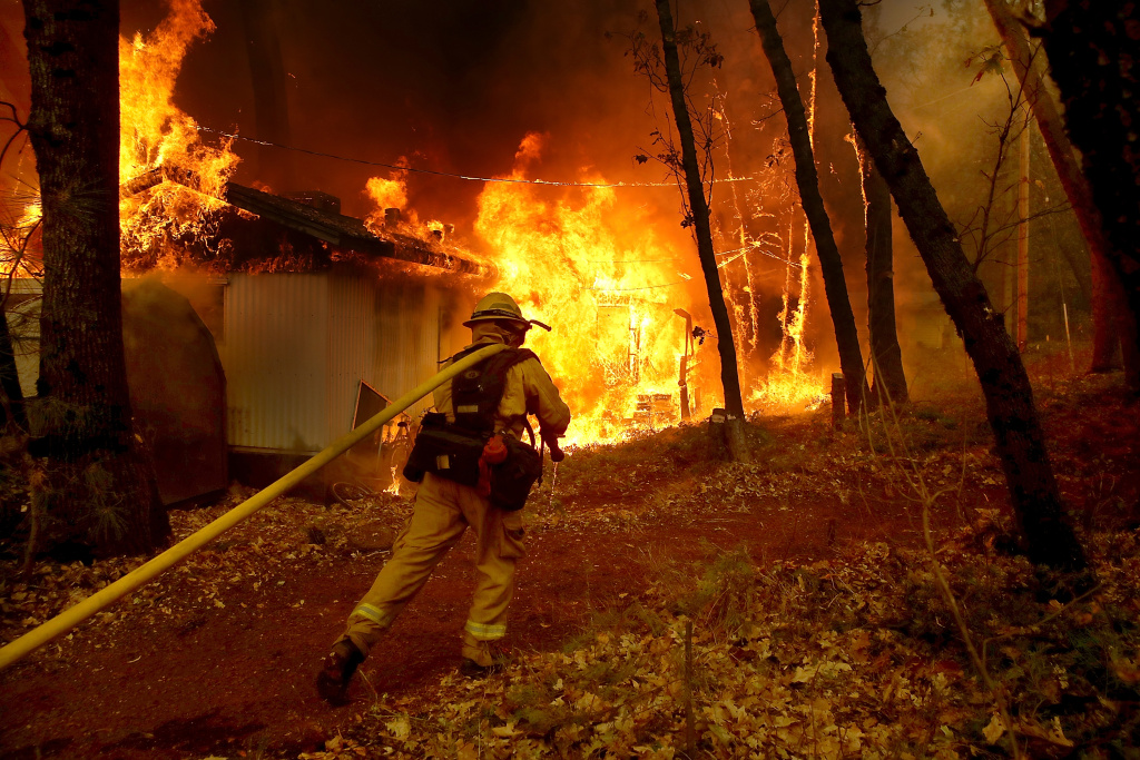 A Cal Fire firefighter pulls a hose towards a burning home as the Camp Fire moves through the area on November 9, 2018 in Magalia, California.