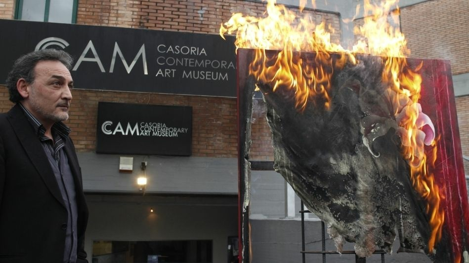 Antonio Manfredi, director of the Museum of Contemporary Art in Casoria, Italy, burns an artwork by French artist Severine Bourguignon.