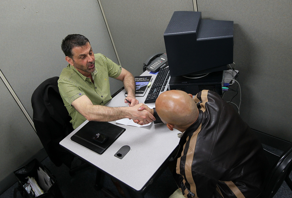 Vince Fortunato (L) shakes hands with a job applicant during a job interview at the Career Link Center One Stop job center May 7, 2010 in San Francisco, California.