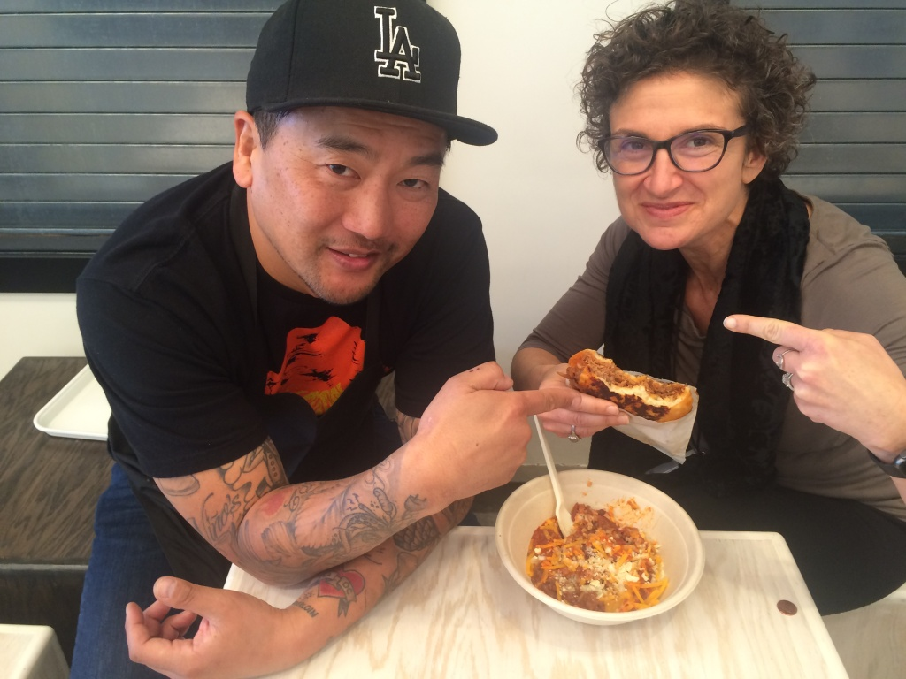 Roy Choi (L) and host Alex Cohen with some of the new foods on the menu at LocoL, Choi's new fast food restaurant opening in the Watts neighborhood on January 18, 2016.