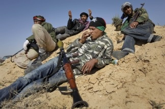 Rebel fighters rest on sand dunes near the front line in Brega, Libya, on April 4, 2011.