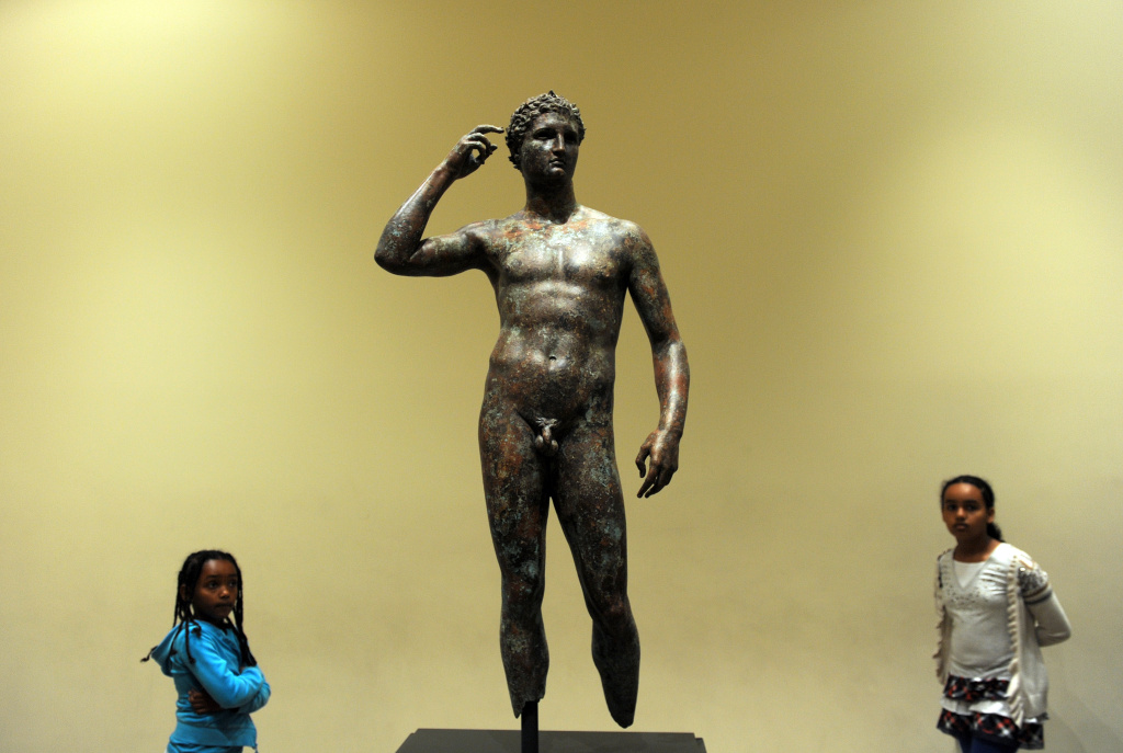 Visitors look on April 18, 2011 at a statue of the Victorious Youth, which was recovered from a first-century BC shipwreck in the Adriatic Sea off the coast of Italy.