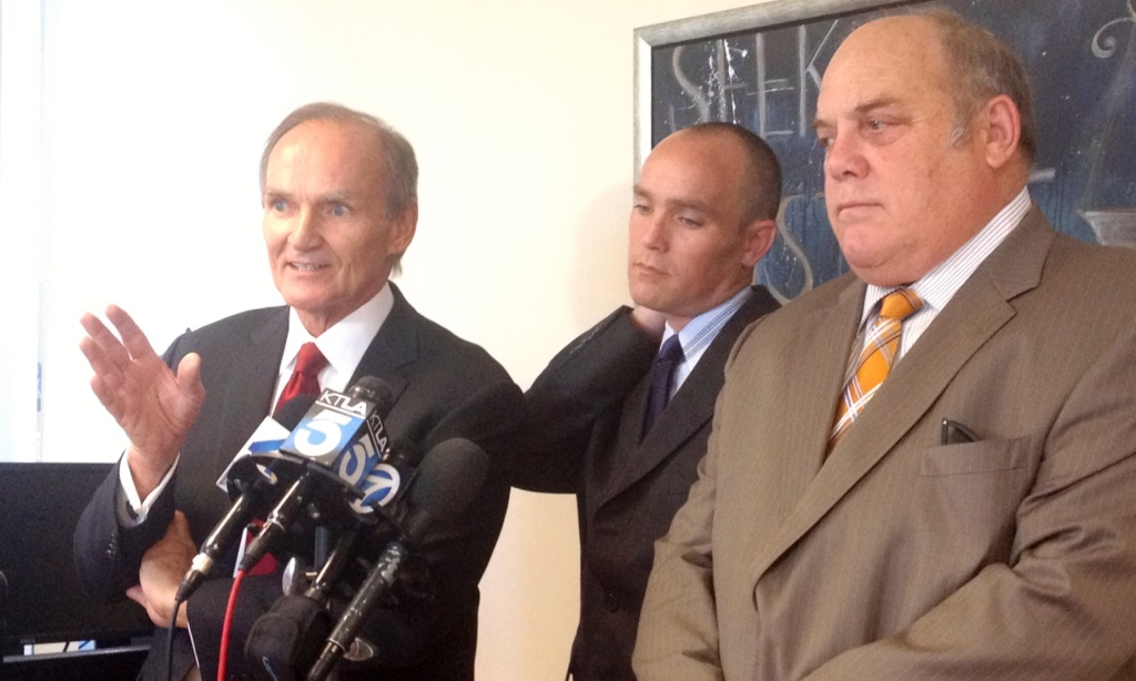 Attorneys Robert Sheahen (left) and Dan Melnick (right) announce a lawsuit filed against the City of Torrance on behalf of their client David Perdue (center) who was rammed into and shot at mistakenly by two Torrance police officers during the search for Christopher Dorner. June 18, 2013.