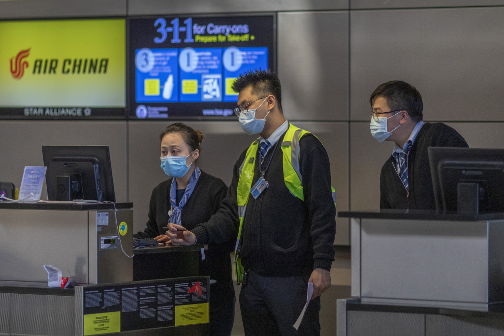 Air China employees wear medical masks for protection against the novel coronavirus outbreak at LAX Tom Bradley International Terminal on February 2, 2020 in Los Angeles, California.