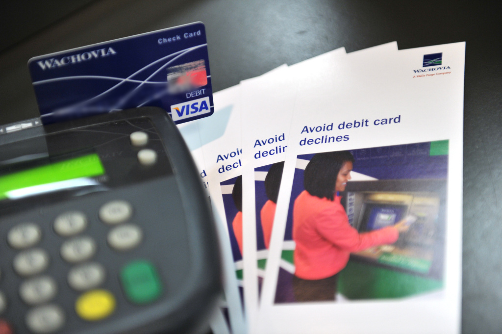 A photo illustration shows a debit card being swiped at a Wachovia Bank on August 20, 2010 in Washington next to a brochure explaining new debit card regulations which went into effect recently.