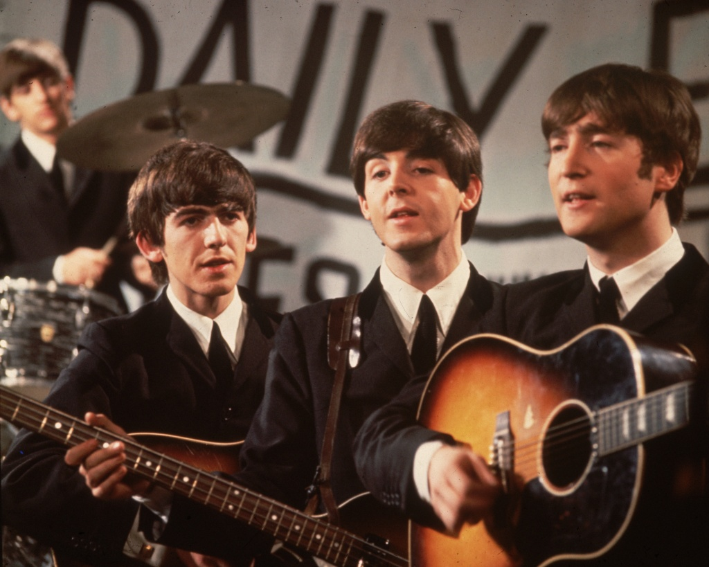 25th November 1963: A group shot of the Beatles, Ringo Starr (in the background), George Harrison (1943 - 2001), Paul McCartney and John Lennon (1940 - 1980), pictured during a performance on Granada TV's Late Scene Extra television show filmed in Manchester, England on November 25, 1963.