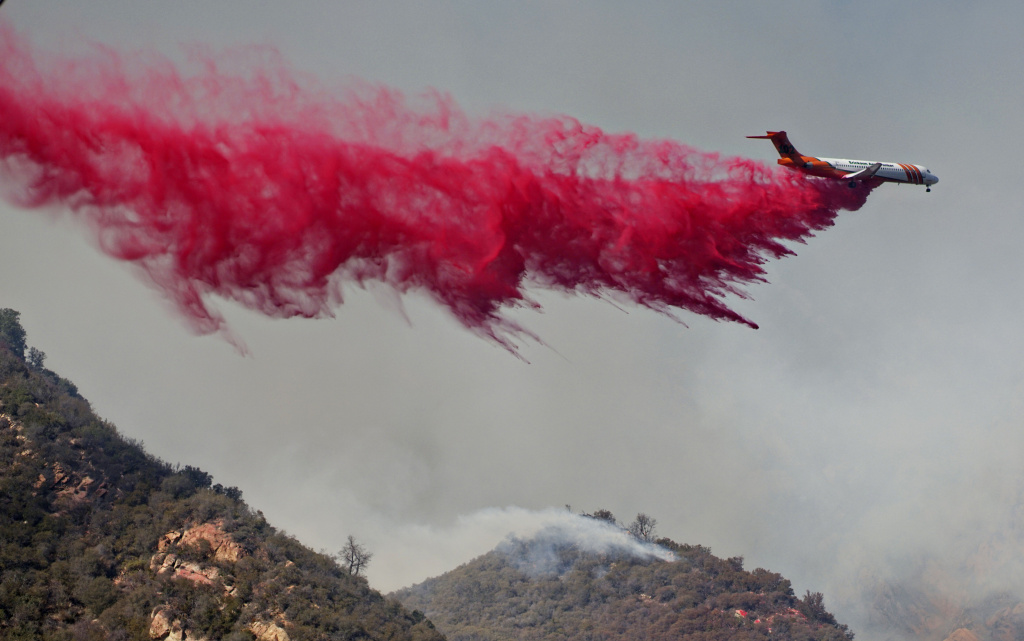 An air tanker drops fire retardant on flames on November 10, 2018 in Malibu, California